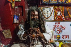 Tantric yogi reciting mantra then drinking whiskey from a skull.